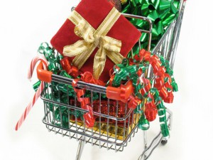 Christmas packages, ornaments candy cane and a bow in a miniature shopping cart.
