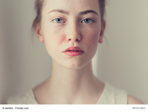 face of a beautiful girl with freckles close-up